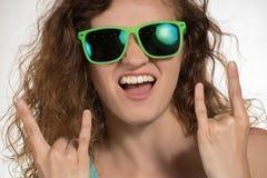 La belle fille avec les cheveux bouclés et dans des lunettes de soleil montre un Th de signe Photographie stock libre de droits