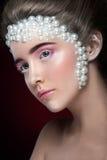 La belle fille avec stupéfier composent et des perles et des fards à paupières roses Photo stock