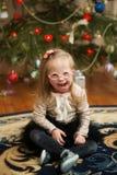 La belle fille avec la trisomie 21 s'assied près d'un arbre de Noël Photos libres de droits