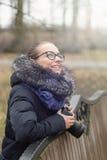 La belle fille avec un appareil-photo marche en parc images stock