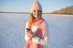 La belle fille avec un téléphone portable en hiver Photographie stock