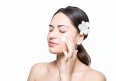 La belle fille avec une fleur dans ses cheveux applique la crème sur le visage Image stock