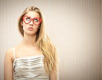 La belle fille blonde avec des verres de coeur rêvent son amour Images libres de droits