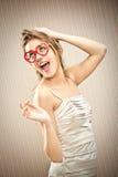 La belle fille blonde avec des verres de coeur rêvent son amour Photographie stock libre de droits