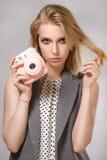 La belle fille blonde avec l'appareil-photo rose rit et sourit Photo stock