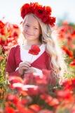 La belle fille blonde d'enfant porte la guirlande des fleurs rouges dans le pré de pavot, printemps Image stock