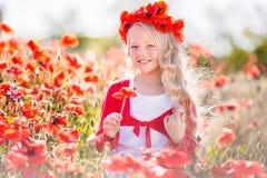 La belle fille blonde d'enfant porte la guirlande des fleurs rouges dans le pré de pavot, printemps Photos stock