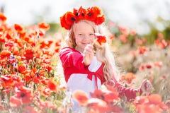 La belle fille blonde d'enfant porte la guirlande des fleurs rouges dans le pré de pavot, printemps Photographie stock