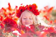 La belle fille blonde d'enfant porte la guirlande des fleurs rouges dans le pré de pavot, printemps Photo stock