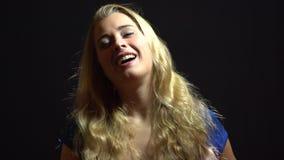 La belle fille blonde sexy dans la robe bleue est chantante et dansante dans le studio avec le fond noir image libre de droits