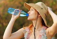 La belle fille boit l'eau Image stock