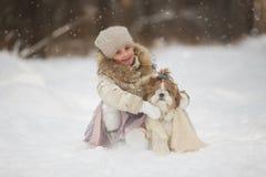La belle fille chauffe le châle de chien dans la forêt de froid d'hiver Photo libre de droits