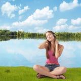 La belle fille dans des écouteurs écoute la musique près de la rivière Images libres de droits
