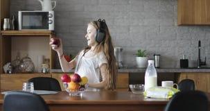 La belle fille dans des écouteurs danse avec le fruit dans la cuisine clips vidéos