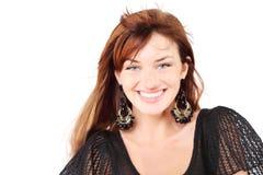 La belle fille dans des boucles d'oreille de robe et d'offre sourit Image libre de droits