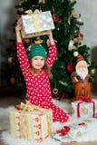 La belle fille dans des pyjamas avec le boîte-cadeau attend Noël et la nouvelle année Photo libre de droits