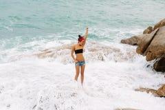 La belle fille dans des shorts courts marchent sur de grandes pierres Image libre de droits