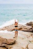 La belle fille dans des shorts courts marchent sur de grandes pierres Photographie stock libre de droits