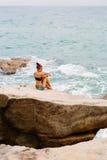 La belle fille dans des shorts courts s'asseyent sur de grandes pierres Image stock