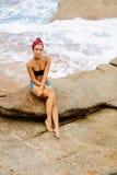 La belle fille dans des shorts courts s'asseyent sur de grandes pierres Images stock