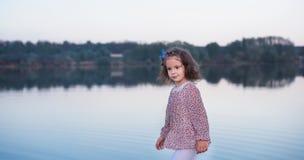 La belle fille dans des vêtements élégants marche pendant l'été près du lac photo stock