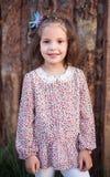 La belle fille dans des vêtements élégants Un portrait du petit enfant dans la perspective des rondins lumineux photo libre de droits