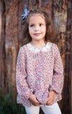 La belle fille dans des vêtements élégants Un portrait du petit enfant dans la perspective des rondins lumineux photographie stock libre de droits