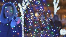 La belle fille dans l'écharpe touche une illumination lumineuse de Noël banque de vidéos