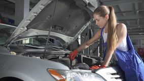 La belle fille dans l'uniforme tourne un tournevis dans un moteur de voiture Concept de service, de réparation, d'entretien et de banque de vidéos