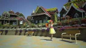La belle fille dans la rétro robe drôle marche dans le jardin d'agrément avec le parapluie coloré d'arc-en-ciel La femme marche l banque de vidéos