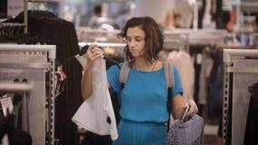 La belle fille dans la robe bleu-clair fait des achats et choisit entre l'achat du T-shirt blanc ou le robe-chemisier gris jeune banque de vidéos
