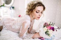 La belle fille dans la robe de dentelle tendre avec le bouquet fleurit des pivoines dans des mains se tenant sur le fond floral d image stock