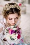 La belle fille dans la robe de dentelle tendre avec le bouquet fleurit des pivoines dans des mains se tenant sur le fond floral d images stock