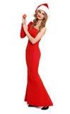 La belle fille dans la robe rouge et le chapeau de Santa d'isolement sur le fond blanc, concept de vacances de Noël, montrent peu Photographie stock