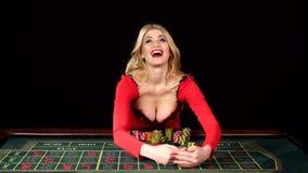 La belle fille dans la robe sexy rouge a gagné au casino noir banque de vidéos