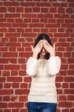 La belle fille dans le chandail blanc ferme ses yeux avec ses mains contre le contexte du mur de briques Copiez l'espace photos libres de droits