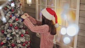 La belle fille dans le chandail et le chapeau tricotés chauds de Santa décore l'arbre de Noël banque de vidéos