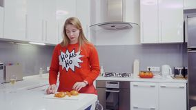 La belle fille dans le chandail rouge coupe le kaki à la cuisine et mange du fruit banque de vidéos