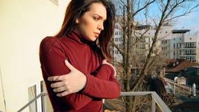 La belle fille dans le chandail rouge se tient sur le balcon clips vidéos