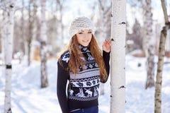 La belle fille dans le chapeau blanc se tient près du bouleau en hiver photographie stock