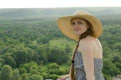 La belle fille dans le chapeau et la robe s'assied sur un fond de forêt d'été Photos stock