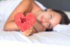 La belle fille dans le lit donne le coeur de la pastèque sur une fourchette images stock