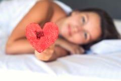 La belle fille dans le lit donne le coeur de la pastèque sur une fourchette photos stock