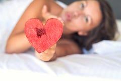 La belle fille dans le lit donne le coeur de la pastèque sur une fourchette image stock