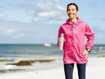 La belle fille dans le sport vêtx l'eau potable après séance d'entraînement sur la plage Photos stock