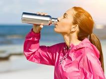 La belle fille dans le sport vêtx l'eau potable après séance d'entraînement sur la plage Photo stock