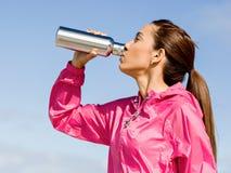 La belle fille dans le sport vêtx l'eau potable après séance d'entraînement sur la plage Photographie stock libre de droits