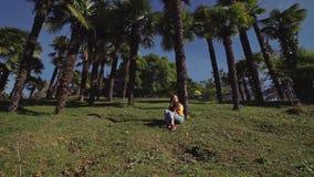 La belle fille dans les jeans et la veste s'assied sur une pelouse verte sous des palmiers banque de vidéos