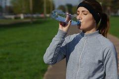 La belle fille dans les vêtements de sport boit l'eau Coureur de femme de forme physique de sport après avoir pulsé Images stock