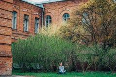 La belle fille dans la pose de lotus s'assied sur le fond d'un vieux bâtiment et d'un jeune arbre de floraison Image stock